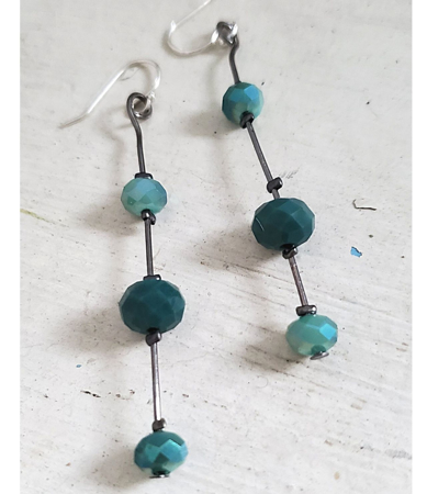 Two tone teal crystal stick earrings on white wood