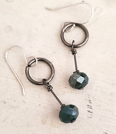 On white wood small gunmetal hoop green crystal earrings
