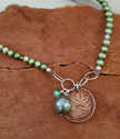 Canadian coin green pearl necklace on wood