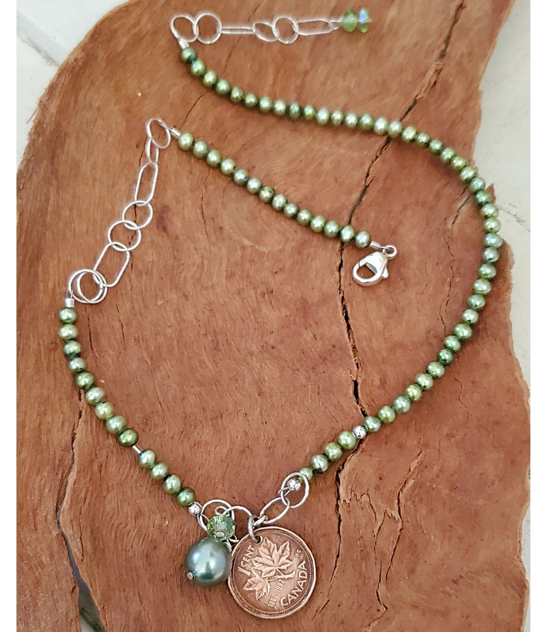 full view Canadian coin green pearl necklace on wood