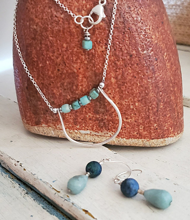 Blue stone silver chain necklace earring set on vase
