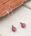 Long silver pink gemstone earrings on wood