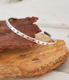 silver XOX bracelet on rocks