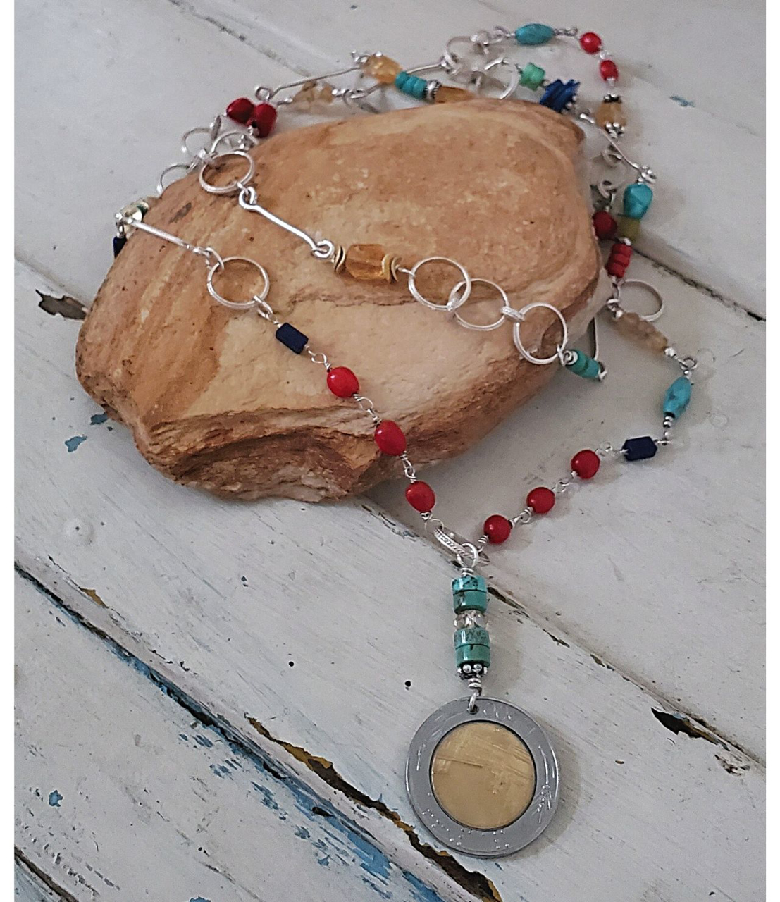 Colorful gemstone long Italian coin necklace on rock
