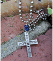 Words stamped on silver cross necklace on brick