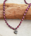 Silver heart purple pearl necklace on wood