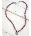 full view Silver heart purple pearl necklace on wood