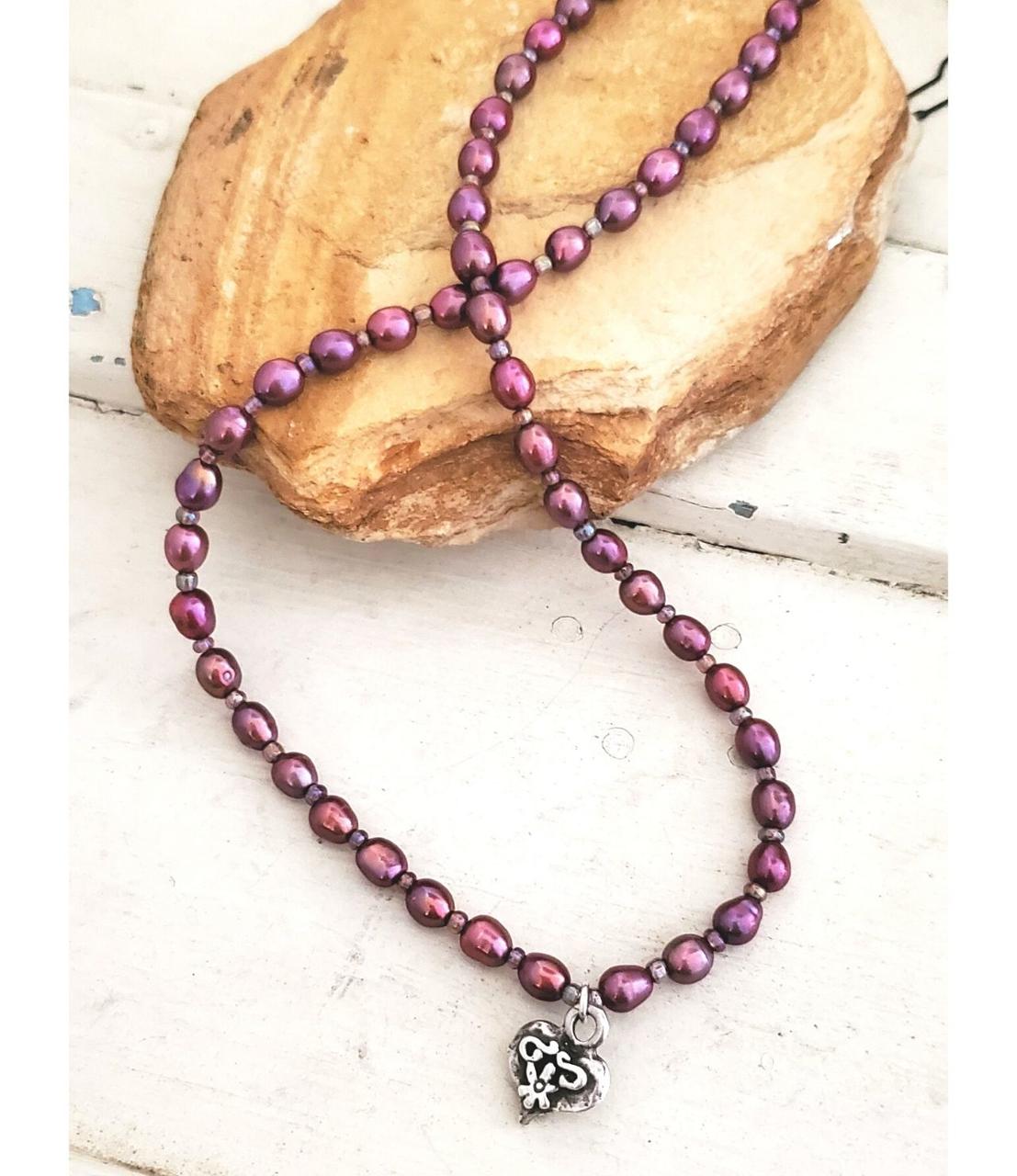 Silver heart purple pearl necklace on rock