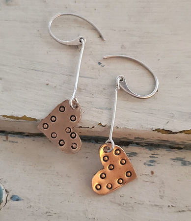 Bronze heart silver stick earrings on white trunk