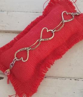 bronze triple heart bracelet on red pillow