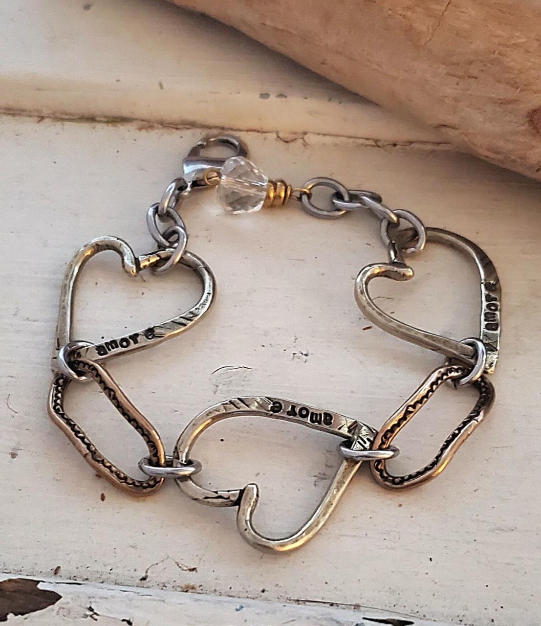 mixed metal triple heart link bracelet on white trunk