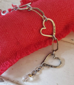 close up crystal on triple heart link bracelet on red pillow