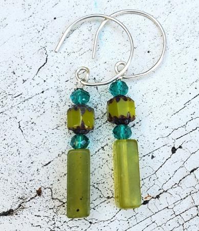 green gemstone stick earrings on white distressed wood