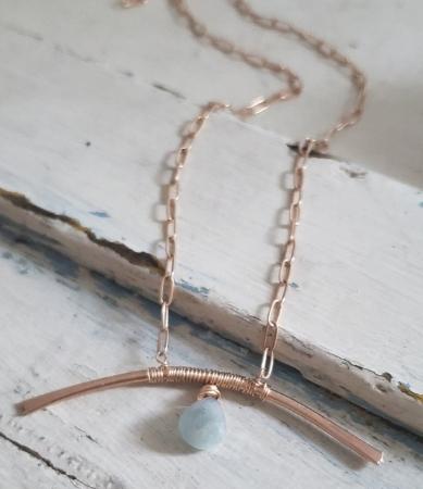 bronze arc bar blue aquamarine necklace on white trunk