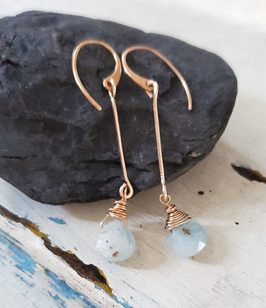 blue gemstone bronze stick earrings on black rock