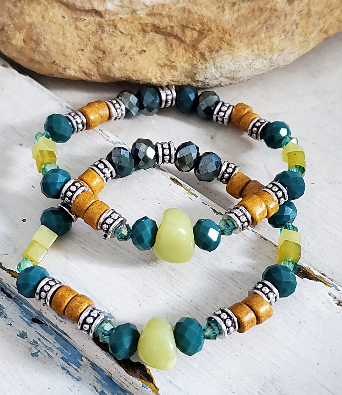 mixed green gemstone bracelet stack against rocks