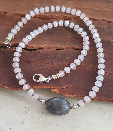 Gray and pink gemstone necklace on wood