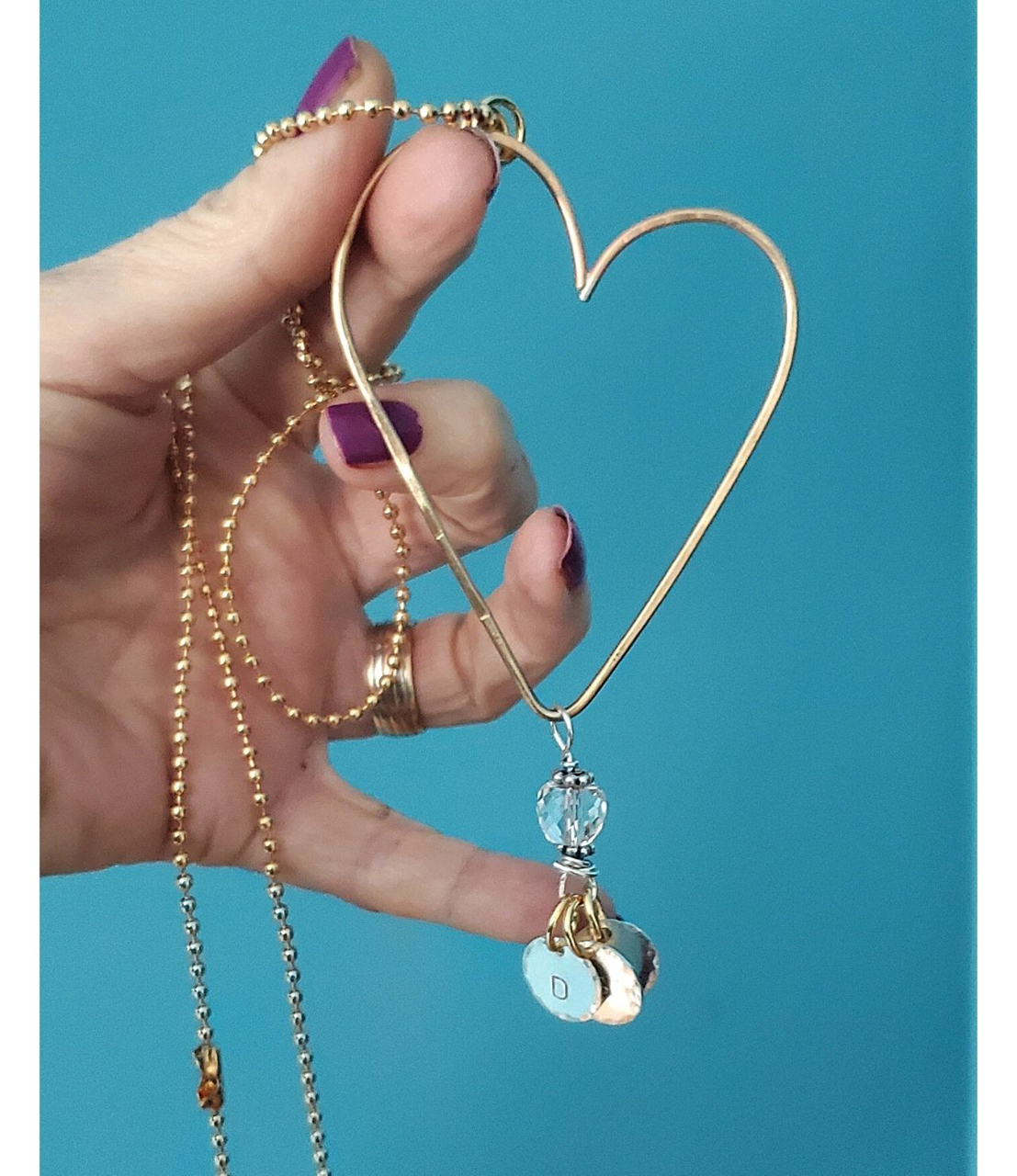hand holding gold heart charm necklace on teal background