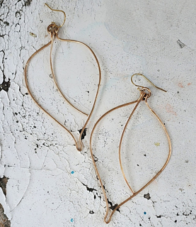 Handcrafted large bronze loose leaf earring on white distressed wood