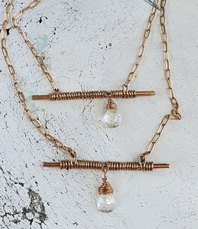 wired wrapped bronze bar crystal chain necklaces on white distressed wood