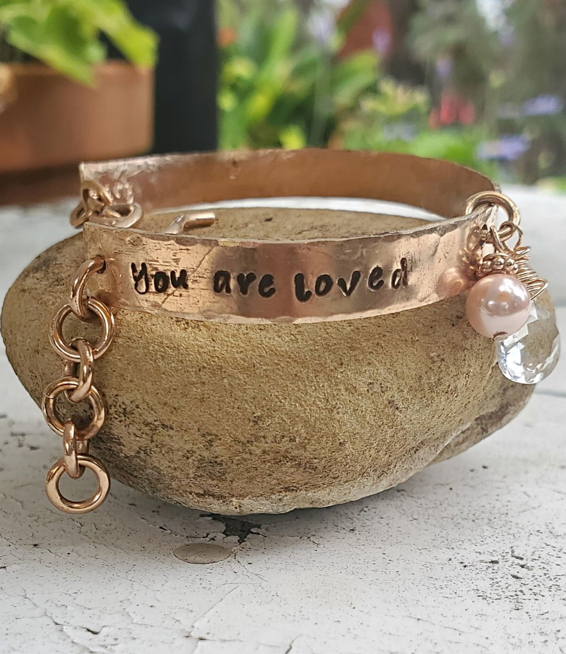 You are Loved bronze pearl crystal bracelet on rock in garden