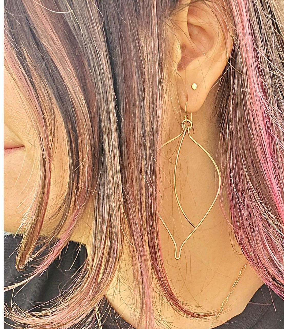 model wearing big bronze wire leaf earrings