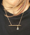 model wearing bronze bar necklace with offset clear stone