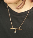 model wearing bronze bar necklace with centered stone