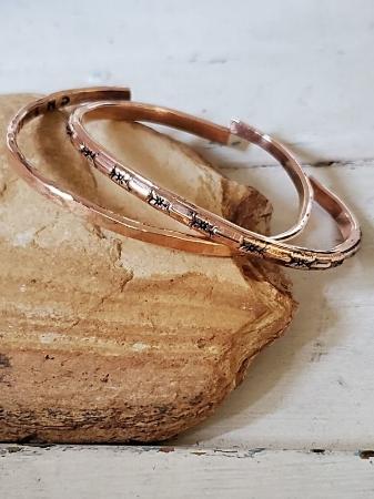 two bronze bracelets on rock