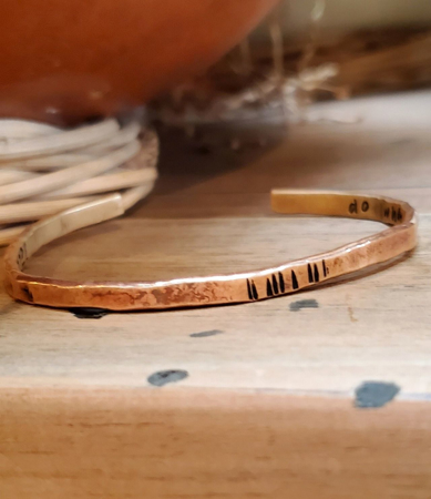 brass line design cuff bracelet on table with pottery