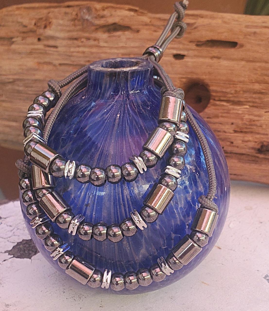 3 stacked black Morse code bracelets on blue vase