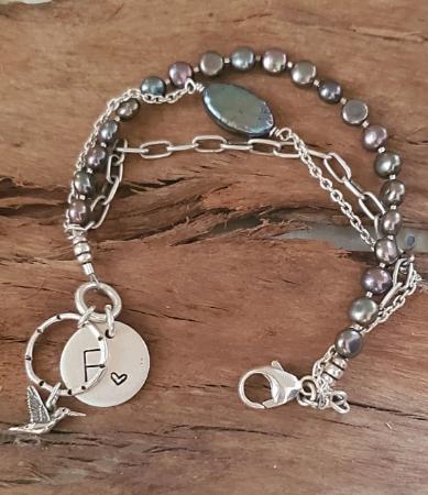 Pearl silver chain hummingbird bracelet on wood