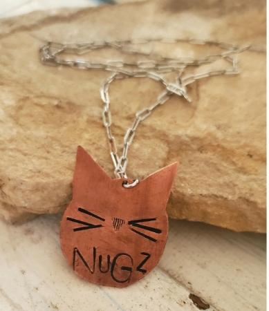 Copper cat face necklace on rock