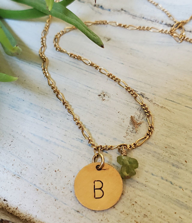 Gold initial charm chain necklace green gemstones on rock