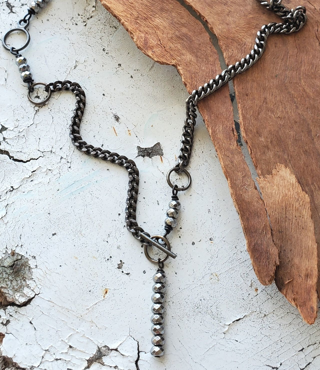 silver stone black chain necklace on wood