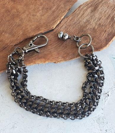 Black gunmetal multi chain bracelet on table