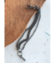Black multi chain bracelet on table