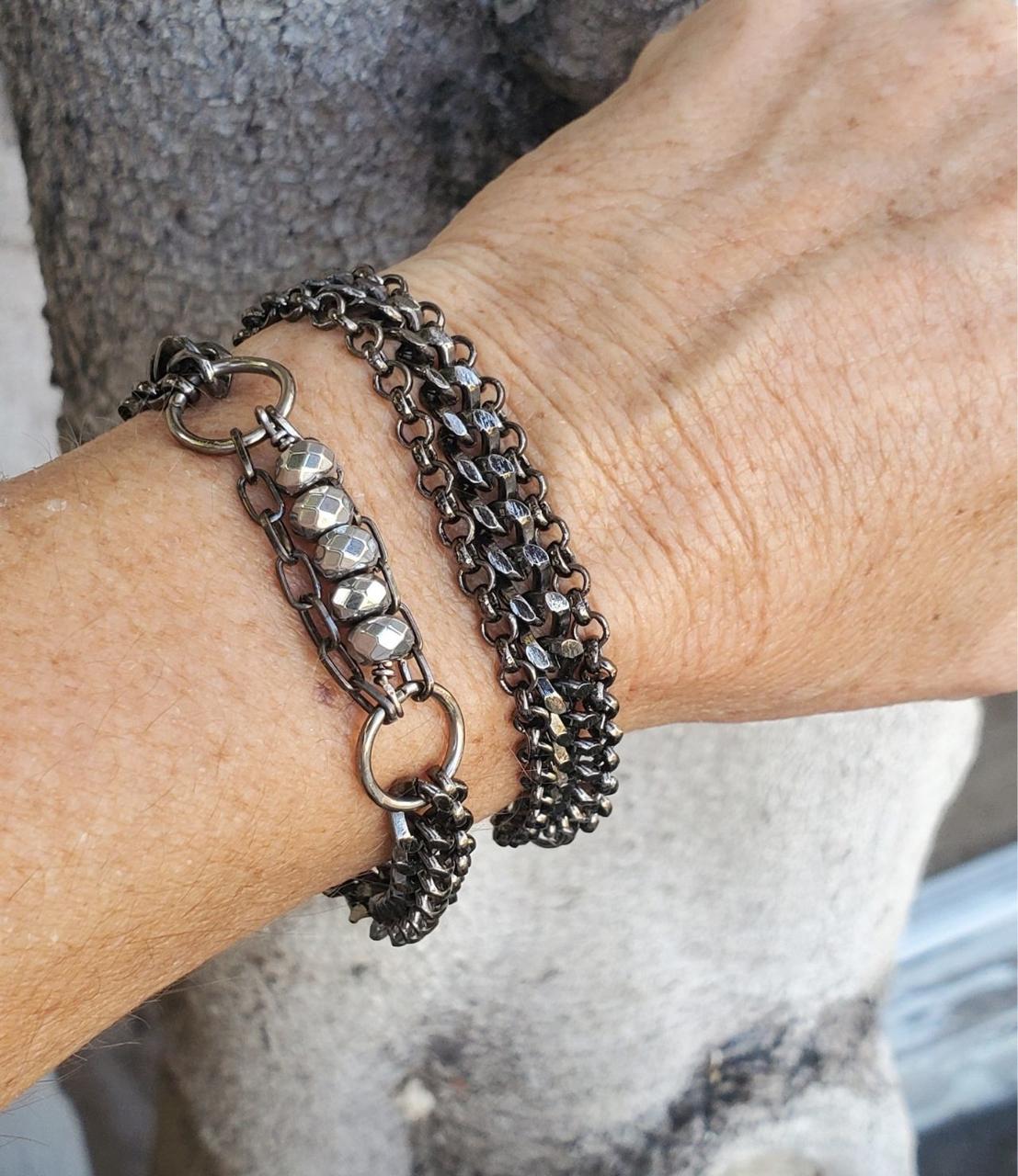 two black multi chain bracelets on wrist