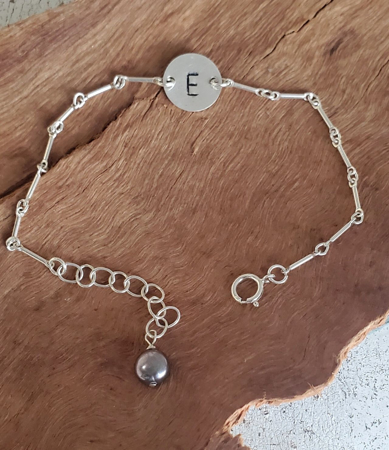 sterling initial bracelet with pearl on wood