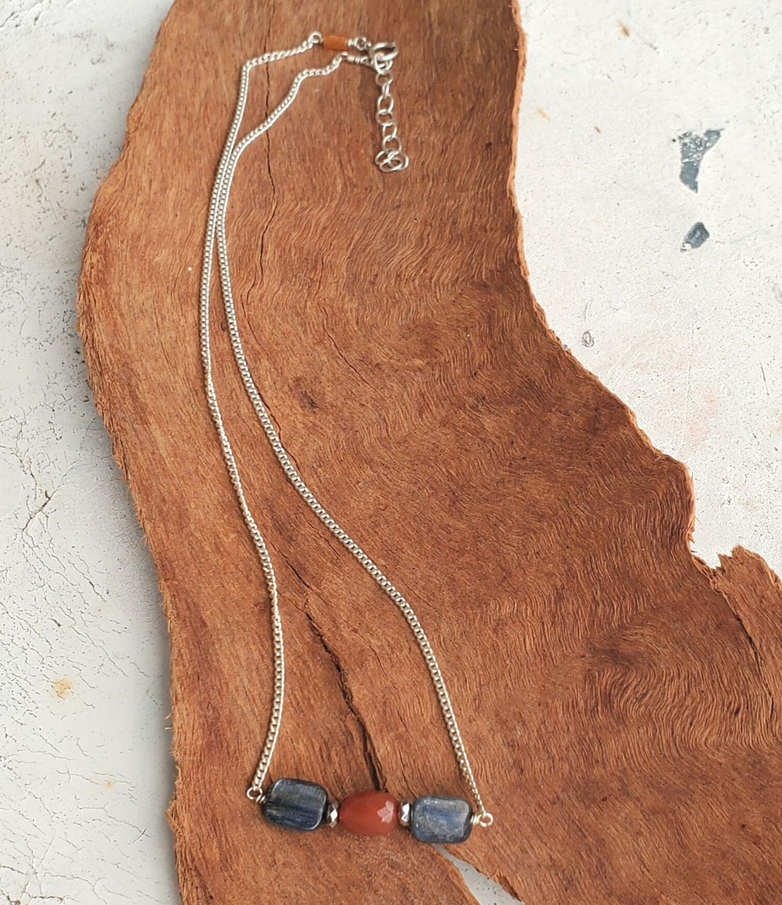 silver chain blue orange gemstone necklace on wood