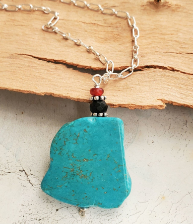 Turquoise pendant silver chain necklace on wood