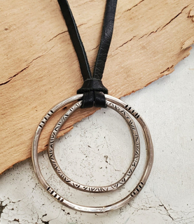 Patterned Silver circles black leather necklace on wood