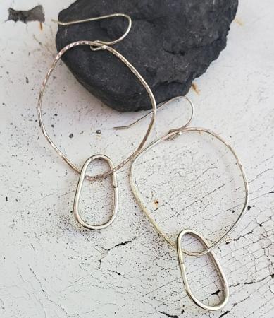 Silver hoop oval earrings on rock