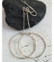 Geometric silver hoop stick earrings on black rock