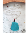 Turquoise pendant silver chain statement on table