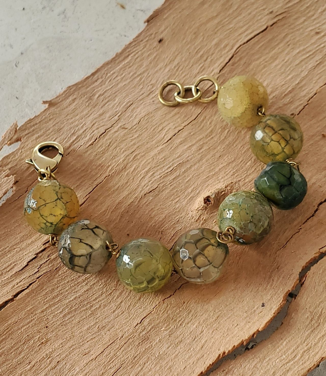 Green and teal round gemstone bracelet on wood