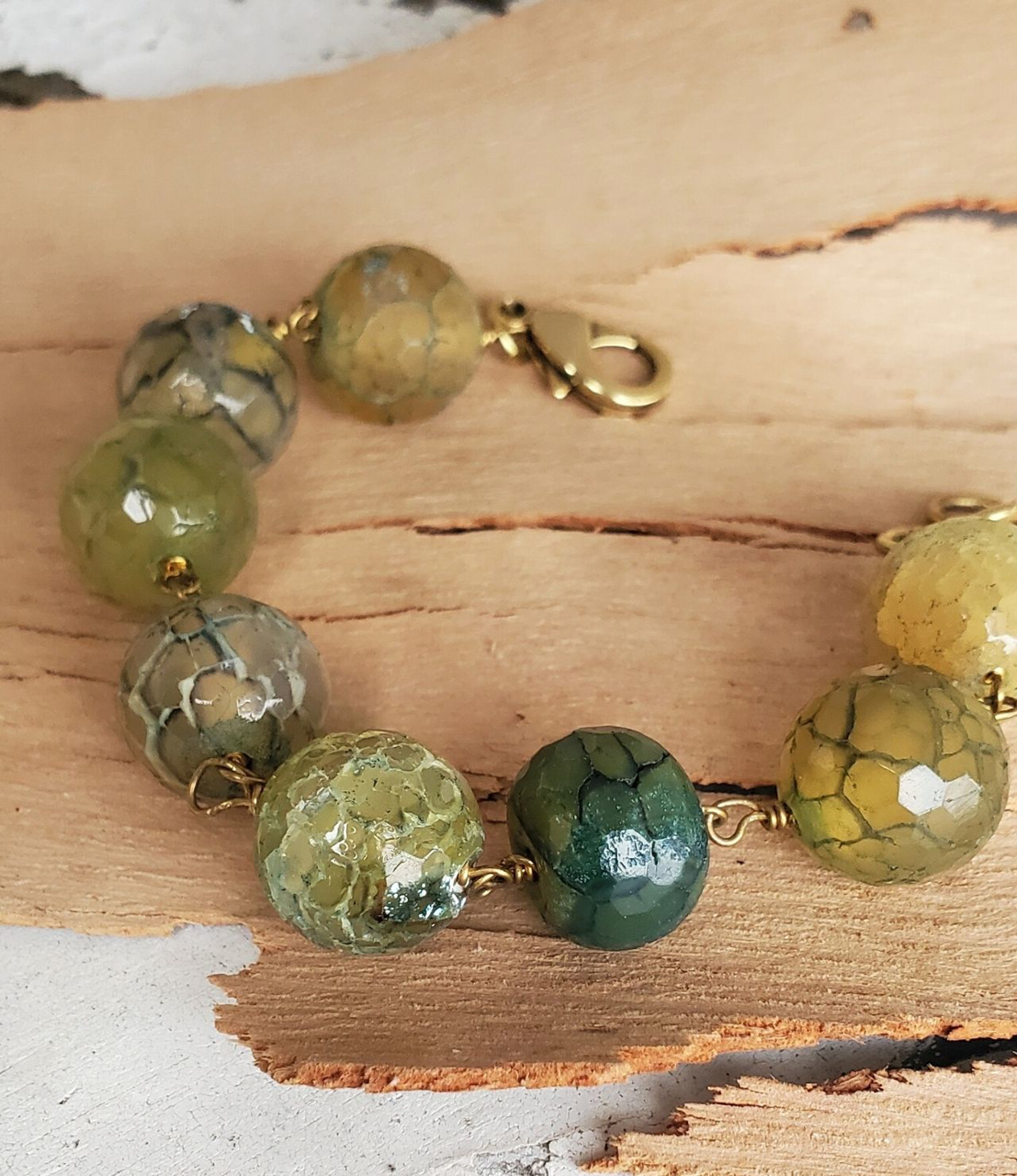 close up of Green and teal round gemstone bracelet on wood