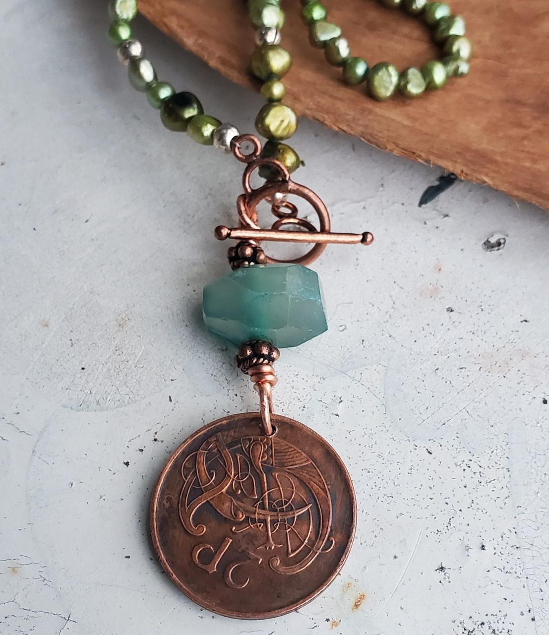 close up old vintage coin design on green pearl necklace on wood