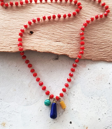 red crystal chain blue, green yellow gemstone necklace on wood