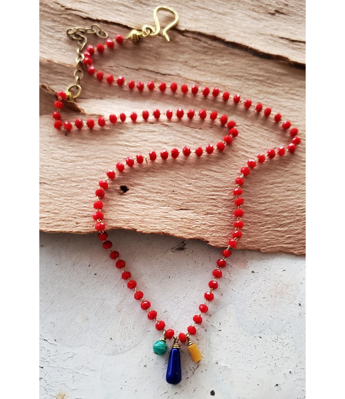 Bright gemstone dainty necklace on wood with red, blue, green, yellow stones